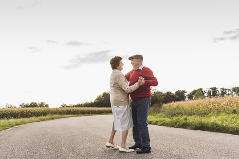 Senior couple dancing on country road - UUF12056