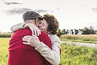 Senior couple hugging in rural landscape - UUF12059
