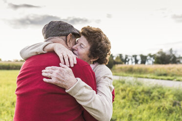 Senior couple hugging in rural landscape - UUF12059