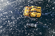 Germany, yellow backpack and lens lying on frozen Lake Koenigssee - MMAF00157