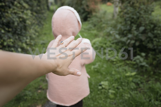 Mother's hand reaching for daughter in garden - KMKF00030