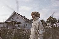 Boy standing in field beside rural house - KMKF00033