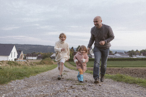 Father with two children running on field path - KMKF00036