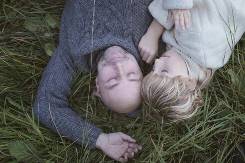 Father with son lying in meadow - KMKF00039