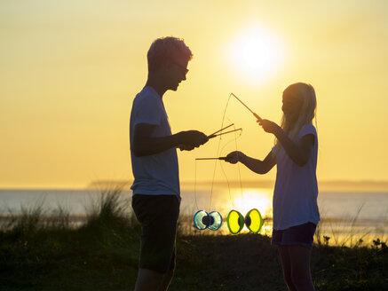 France, Bretagne, Sainte-Anne-la-Palud, La Plage de Treguer, brother and sister juggling with diabolo at sunset - LAF01923