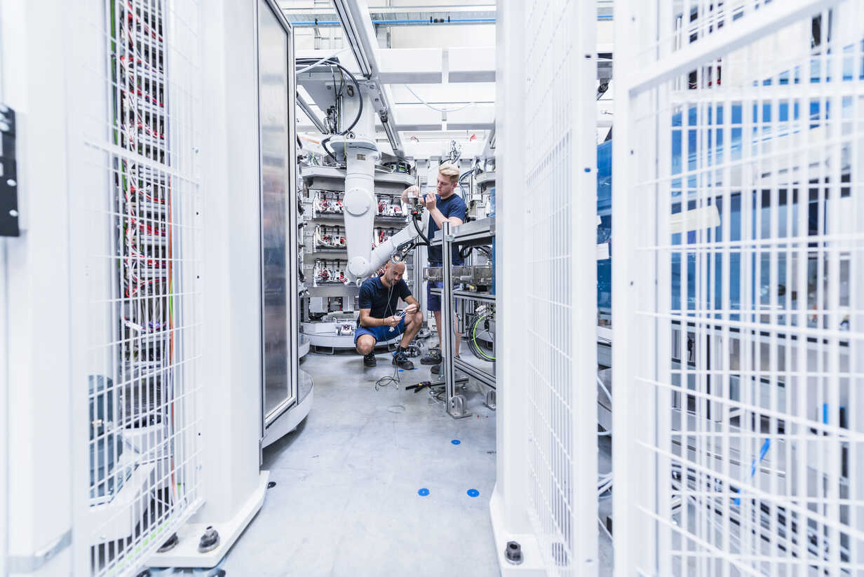 Two colleagues working at industrial robot in modern factory - DIGF02936 - Daniel Ingold/Westend61