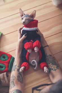 Close-up of woman holding Sphynx cat wearing pullover - RTBF01061