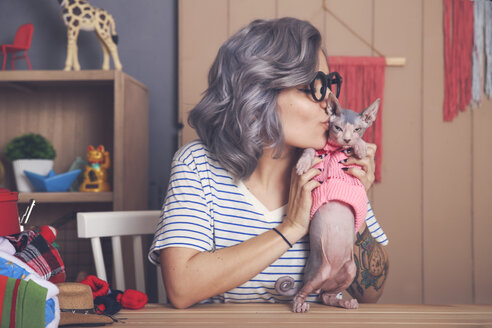 Young woman holding and kissing Sphynx cat wearing pullover - RTBF01070
