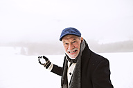 Portrait of senior man holding snowball - HAPF02227