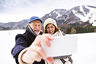 Senior couple kissing taking selfie with cell phone in winter landscape - HAPF02236