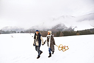 Happy senior couple with sledge walking in snow-covered landscape - HAPF02245