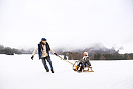 Senior couple having fun with sledge  in snow-covered landscape - HAPF02248