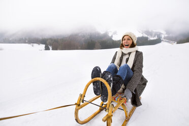 Laughing senior woman sitting on sledge in snow-covered landscape - HAPF02251