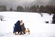 Back view of senior couple sitting side by side on sledge in snow-covered landscape - HAPF02254