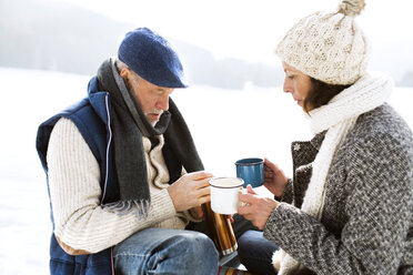 Senior couple having a break with hot beverages in snow - HAPF02257