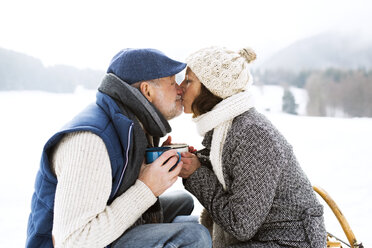 Kissing senior couple sitting on sledge in snow-covered landscape - HAPF02260