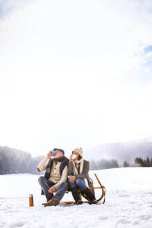 Back view of senior couple sitting side by side on sledge in snow-covered landscape drinking hot beverages - HAPF02266