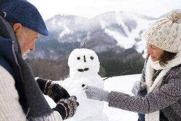 Senior couple building up snowman in winter landscape - HAPF02269