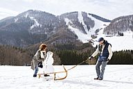 Senior couple with snowman on sledge in winter landscape - HAPF02272