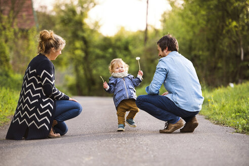 Cute little boy with parents on field path - HAPF02311
