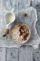 Bowl of granola with nuts and a jug of milk - MYF01972