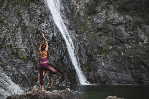 Italy, Lecco, woman doing Tree Yoga Pose on a rock near a waterfall - MRAF00250