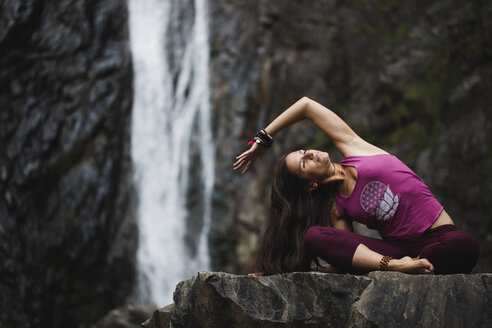 Italy, Lecco, woman doing yoga practice near a waterfall - MRAF00253