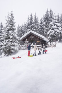 Austria, Altenmarkt-Zauchensee, family with sledges at wooden house at Christmas time - HHF05489
