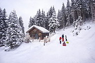 Austria, Altenmarkt-Zauchensee, family with sledges at wooden house at Christmas time - HHF05492