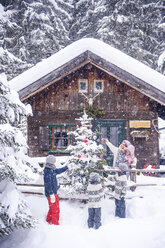 Austria, Altenmarkt-Zauchensee, family decorating Christmas tree at wooden house - HHF05495