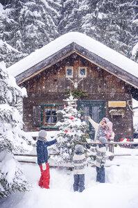 Austria, Altenmarkt-Zauchensee, family decorating Christmas tree at wooden house - HHF05495