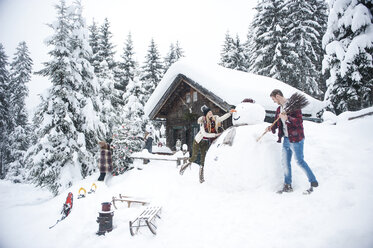 Austria, Altenmarkt-Zauchensee, friends building up big snowman at wooden house - HHF05499