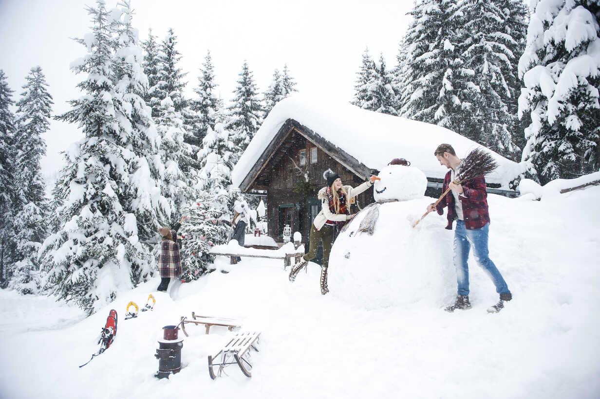 Austria, Altenmarkt-Zauchensee, friends building up big snowman at wooden house - HHF05499 - Hans Huber/Westend61