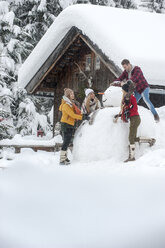 Austria, Altenmarkt-Zauchensee, friends building up big snowman at wooden house - HHF05502