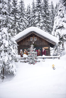 Austria, Altenmarkt-Zauchensee, friends decorating Christmas tree at wooden house - HHF05505