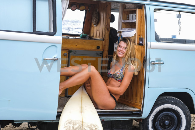 Portrait of happy young woman with surfboard in van - SIPF01801