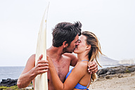 Young couple with surfboard kissing on the beach - SIPF01810