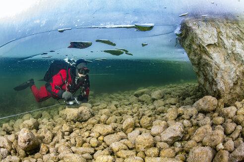 Austria, Styria, Lake Grundlsee, scuba diver under ice floe - YRF00166
