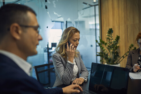 Businesswoman on cell phone during a meeting - ZEDF00911