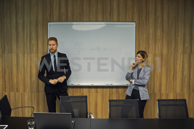 Businessman and businesswoman leading a presentation in boardroom - ZEDF00917