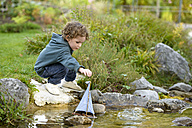 Toddler playing with a toy boat in a brook - LBF01694
