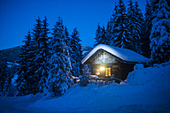 Austria, Altenmarkt-Zauchensee, sledges, snowman and Christmas tree at illuminated wooden house in snow at night - HHF05514