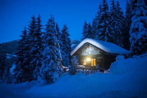 Austria, Altenmarkt-Zauchensee, sledges, snowman and Christmas tree at illuminated wooden house in snow at night - HHF05514