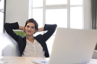 Happy businesswoman sitting in office, looking at laptop with hands behind head - FKF02607