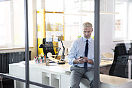 Mature businessman sitting office , using smartphone, reading messages - FKF02613