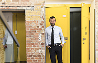 Businessman leaning in front of elevator with hands in pockets - FKF02625