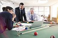 Business people standing at pool table with laptop, discussing investment strategy - FKF02640