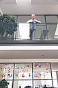 Successful businessman standing at railing in his office - FKF02655