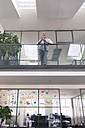 Successful businessman standing at railing in his office, using smartphone - FKF02658