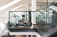 Businessman sitting on floor in the office, taking a break - FKF02691